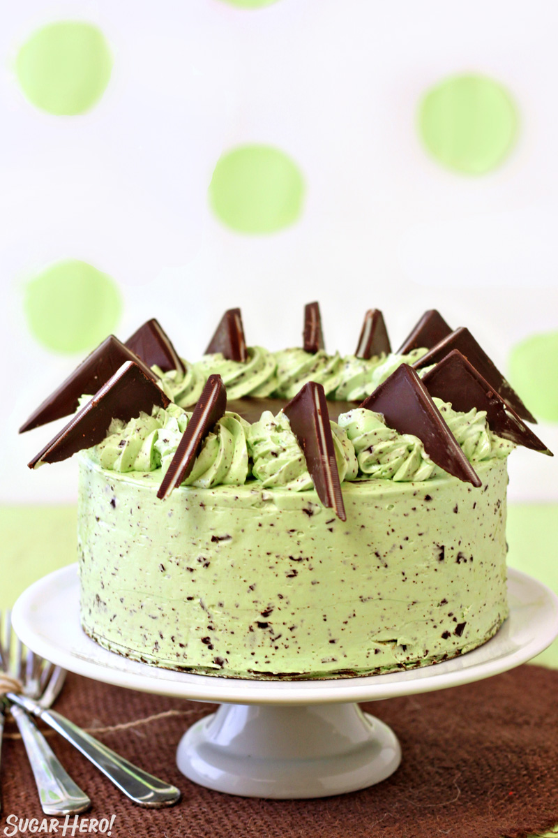 Mint chocolate chip cake with Andes mints on top, displayed on a white cake stand
