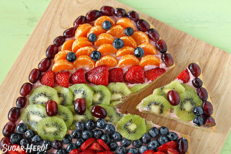 Easter Egg Fruit Pizza on a wooden cutting board with a slice removed