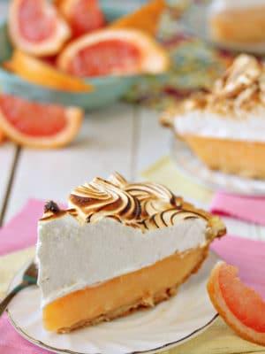Grapefruit Meringue Pie slice with grapefruit slices in the background