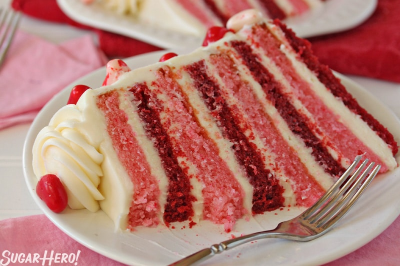 Sky-High Pink and Red Velvet Cake - A piece of cake on a plate displaying the red and pink stripes throughout with a bite taken out of it. | From SugarHero.com