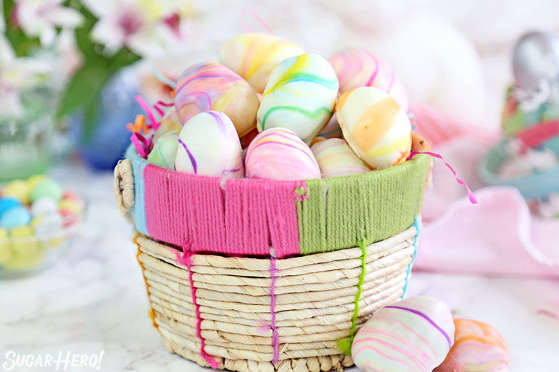 Marbled Easter Egg Truffles - Truffles displayed in basket, showing the pastel colors swirled throughout. | From SugarHero.com