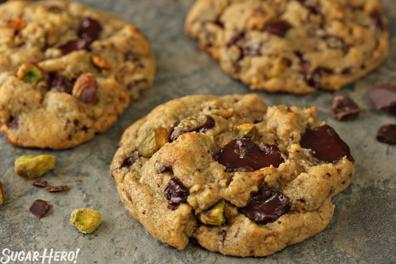 Pistachio Chocolate Chunk Cookies- A shot of three cookies with pistachios sprinkled on top.   From SugarHero.com