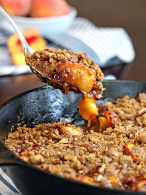 Spoon taking a big scoop of peach cobbler out of a cast iron skillet