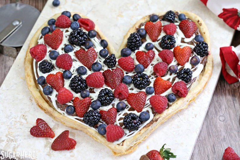 Nutella Puff Pastry Pizza is easy and gourmet. You'll love the combination of buttery puff pastry, Nutella, white chocolate, and juicy fresh berries! | From SugarHero.com
