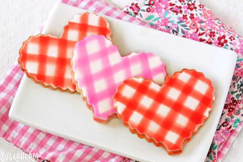 Brown Butter Heart Cookies - three cookies with a gingham pattern on a white plate | From SugarHero.com