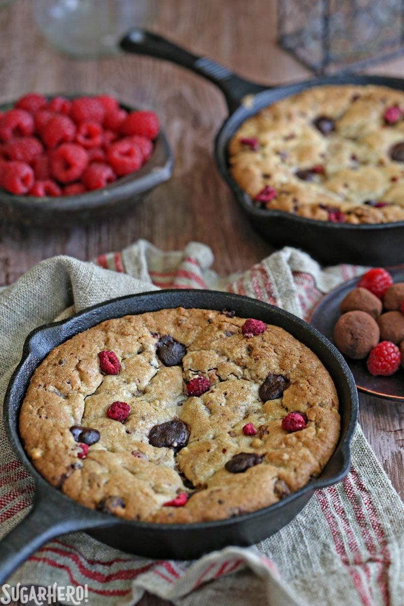 Raspberry Truffle Skillet Cookies - packed with gooey chocolate truffles, raspberries, and nuts! | From SugarHero.com