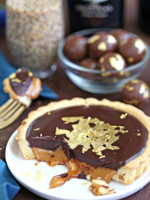 Bailey's Chocolate Caramel Tarts on white plate with bottle of Baileys behind it