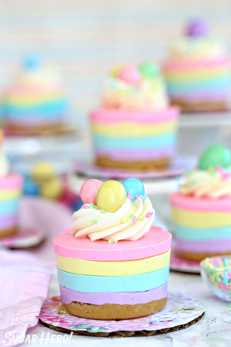 Multiple cheesecakes displayed with pastel stripes and whipped cream on top