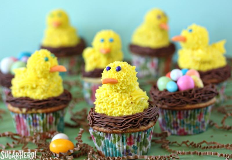 Spring Chick Cupcakes -Multiple cupcakes displayed with a spring chick on top. | From SugarHero.com