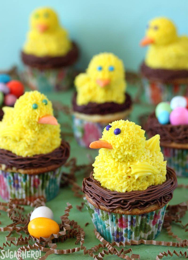 Spring Chick Cupcakes - Multiple cupcakes displayed with a spring chick on top. | From SugarHero.com
