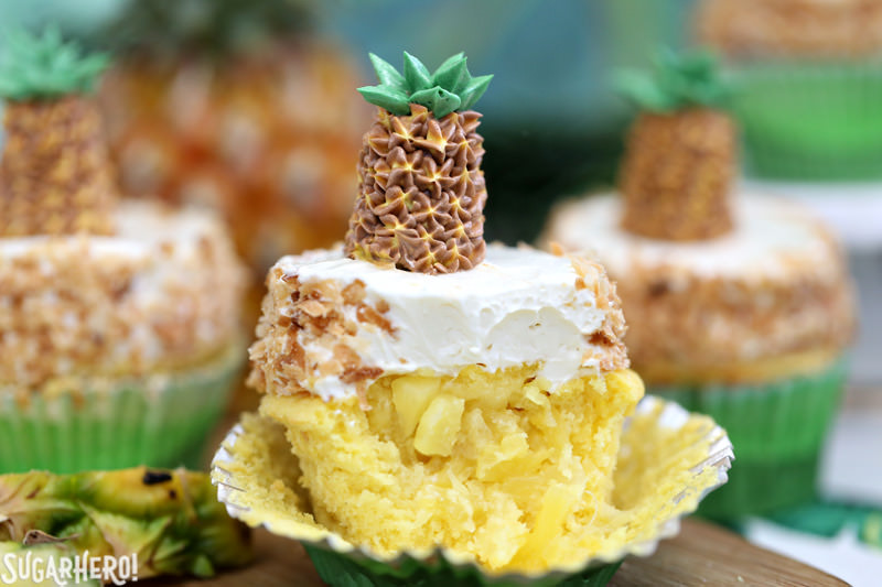 Pineapple Cupcake with coconut buttercream and fresh pineapple spilling out of the center | From SugarHero.com