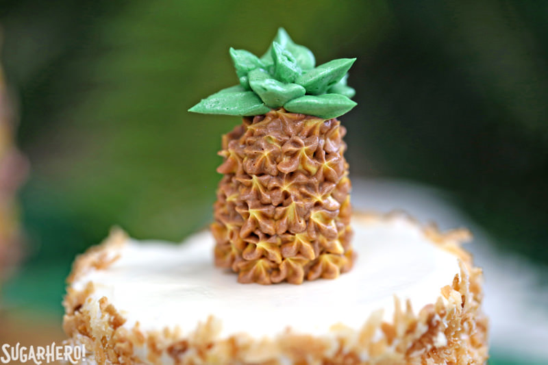 Close-up of buttercream pineapple on top of pineapple cupcakes | From SugarHero.com