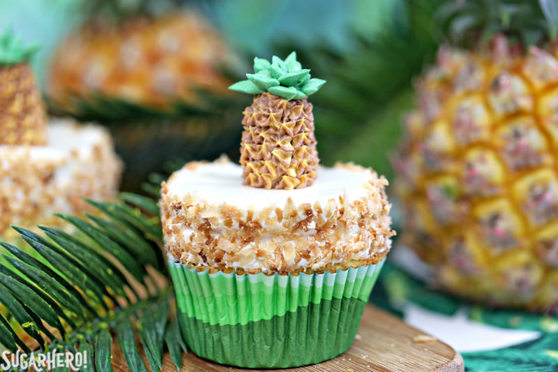 Pineapple Cupcakes - fun and tropical pineapple cupcakes with coconut frosting. Plus an adorable buttercream pineapple on top! | From SugarHero.com
