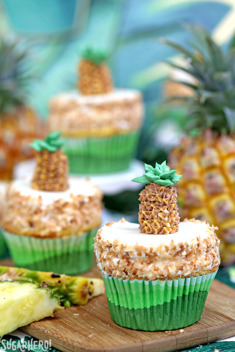 Group of three Pineapple Cupcakes with fresh pineapple in the background | From SugarHero.com