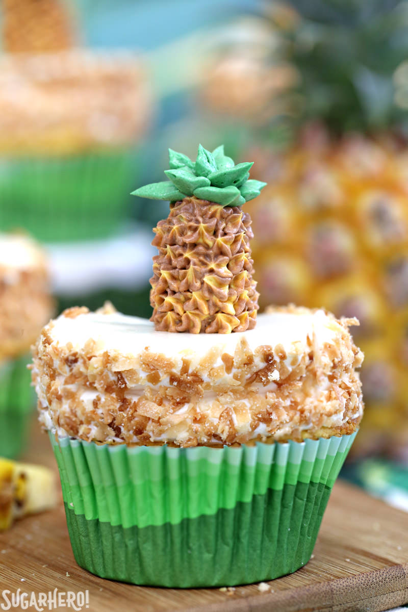 Close-up of a single pineapple cupcake with coconut frosting and a buttercream pineapple on top | From SugarHero.com
