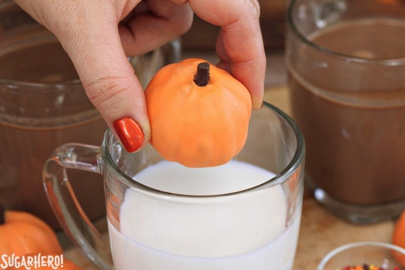 Pumpkin Spice Hot Chocolate Truffles - adding a pumpkin spice truffle to a mug of warm milk to make pumpkin spice hot chocolate | From SugarHero.com