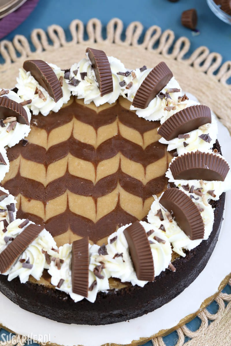 Chocolate Peanut Butter Cheesecake with whipped cream and peanut butter cups on top | From SugarHero.com