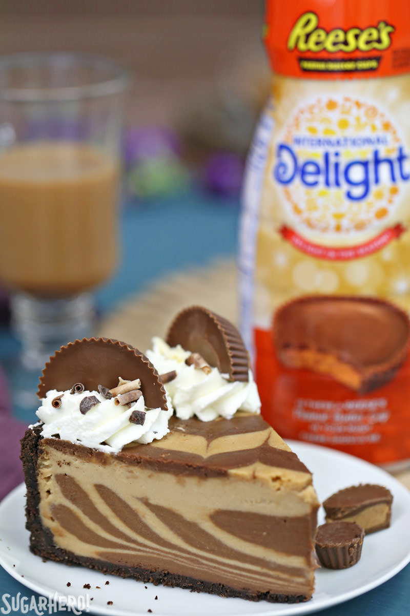 Chocolate Peanut Butter Cheesecake - single slice with peanut butter cup creamer in background | From SugarHero.com