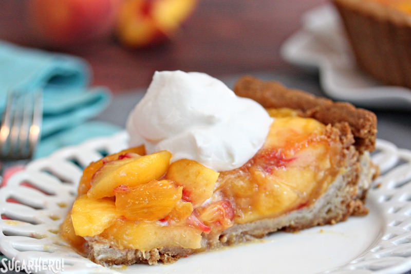 A close-up on a slice of no-bake Fresh Peach Tart, topped with whipped cream | From SugarHero.com