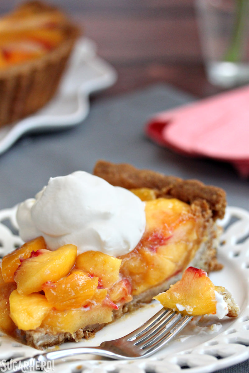 A sslice of no-bake Fresh Peach Tart, topped with whipped cream, with the whole tart in the background | From SugarHero.com