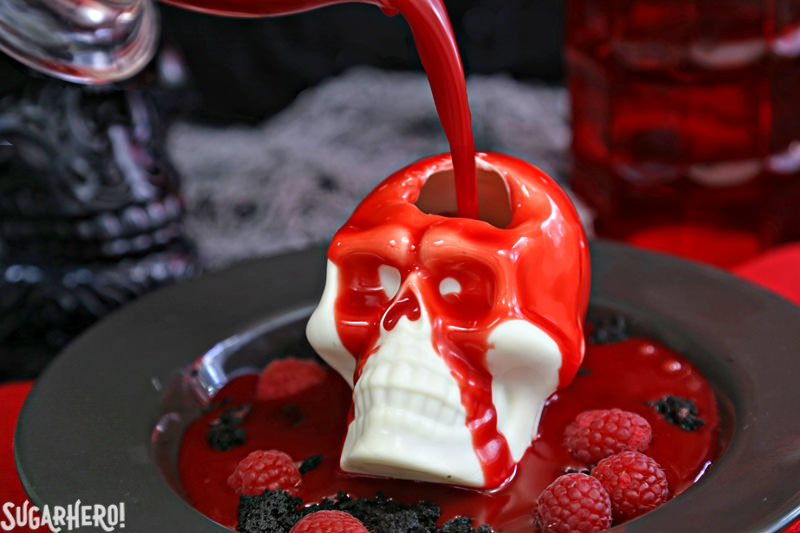 Melting Chocolate Skulls – warm red ganache creating a hole in the top of the white chocolate skull | From SugarHero.com