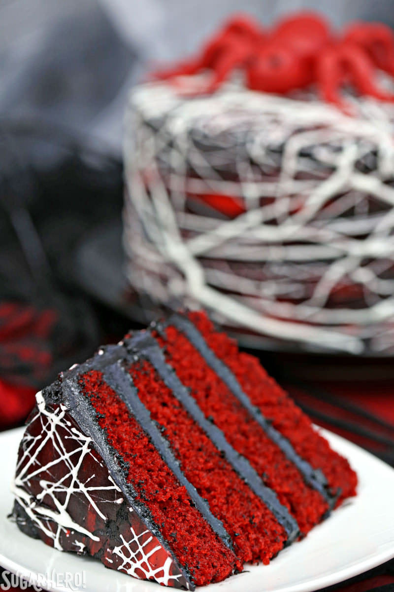 Red Velvet Marshmallow Spiderweb Cake - close-up of slice in foreground with whole cake in background | From SugarHero.com