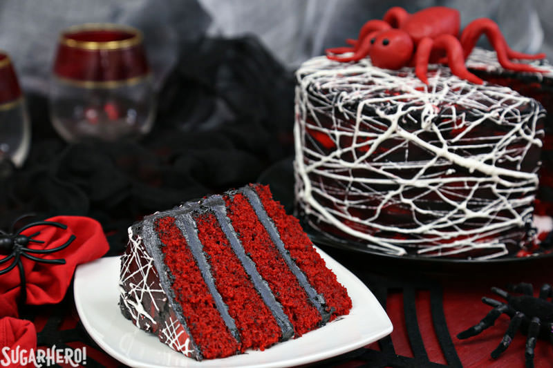 Red Velvet Marshmallow Spiderweb Cake - slice of cake on a plate with full cake behind it | From SugarHero.com
