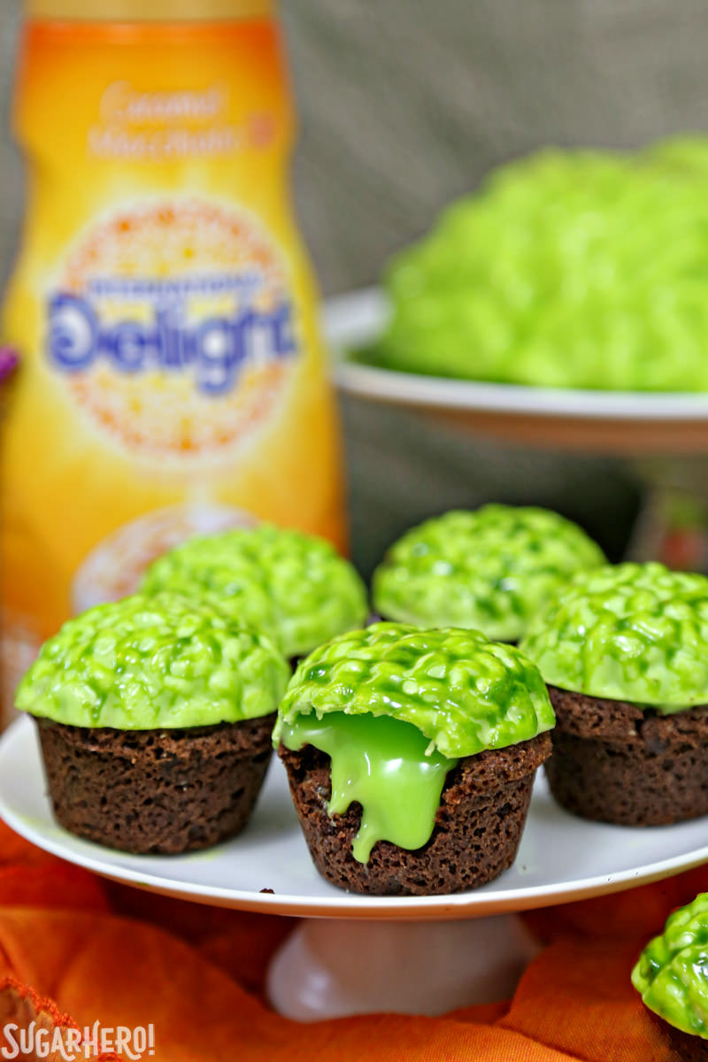 Zombie Brain Brownie Bites - with large green brain behind and caramel coffee creamer bottle | From SugarHero.com