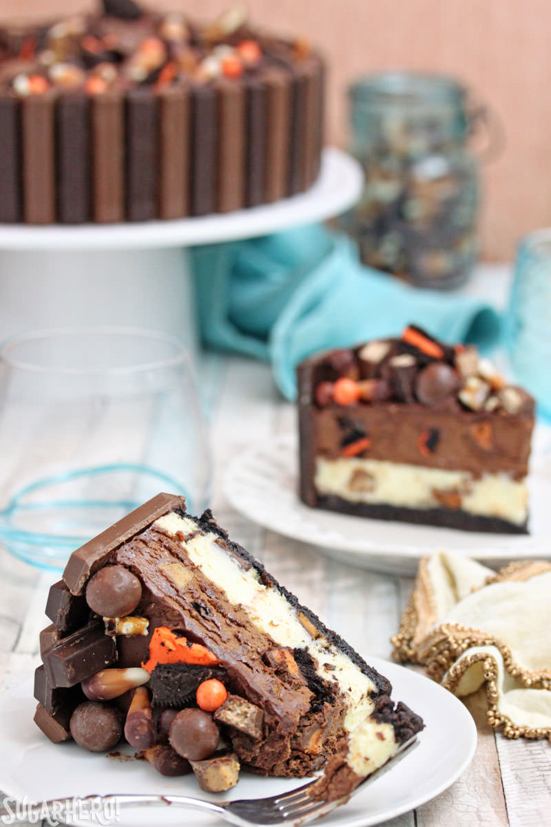 Candy Bar Cheesecake – two cake slices, one with a bite taken out of it | From SugarHero.com