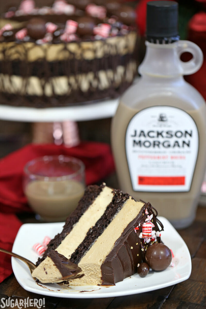 Peppermint Mocha Mousse Cake - slice of mousse cake with a bite taken out of it and whole cake in the background | From SugarHero.com