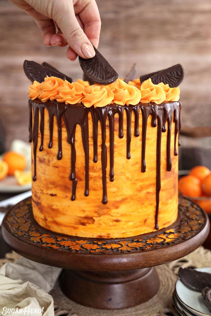 Chocolate Orange Cake - hand putting a chocolate orange slice on top of the decorated chocolate orange cake | From SugarHero.com