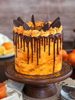 Chocolate Orange Cake on a wooden cake stand in front of a wooden background