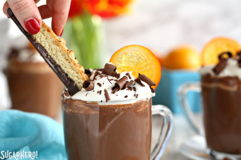 Hand dipping chocolate biscotti into a mug of Orange Hot Chocolate  | From SugarHero.com
