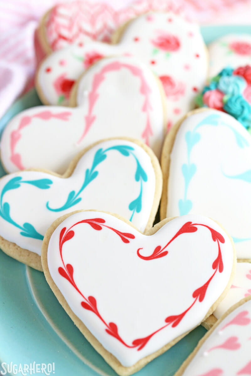 Valentine's Day Sugar Cookies - sugar cookies with a pretty heart border made out of royal icing | From SugarHero.com