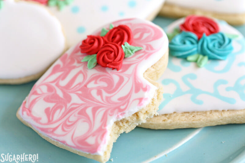 Valentine's Day Sugar Cookies - close-up of sugar cookies with royal icing decorations | From SugarHero.com