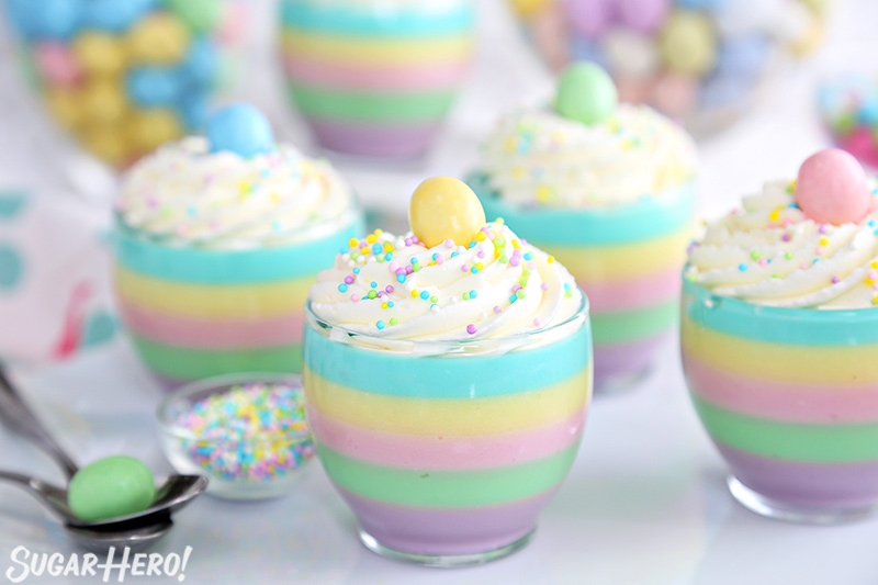 Pastel Rainbow Gelatin Cups – group of striped pastel gelatin cups all arranged together | From SugarHero.com