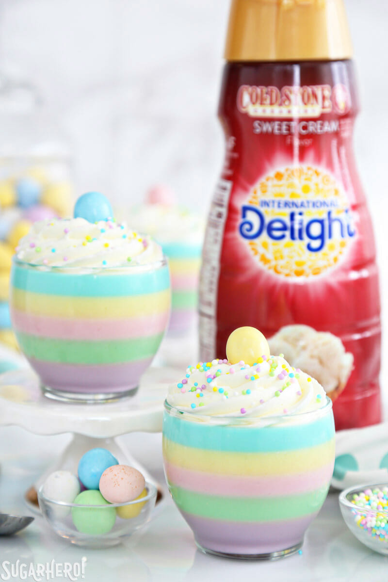 Pastel Rainbow Gelatin Cups – two gelatin cups with coffee creamer bottle in the background | From SugarHero.com