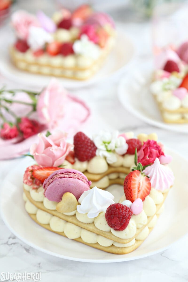 Trendy Cream Tarts - close-up shot of a cream biscuit with meringues, macarons, berries, and more on top | From SugarHero.com