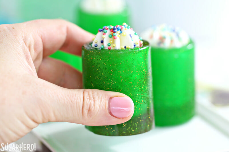 DIY Candy Shot Glasses - raising a candy glass filled with whipped cream and sprinkles | From SugarHero.com