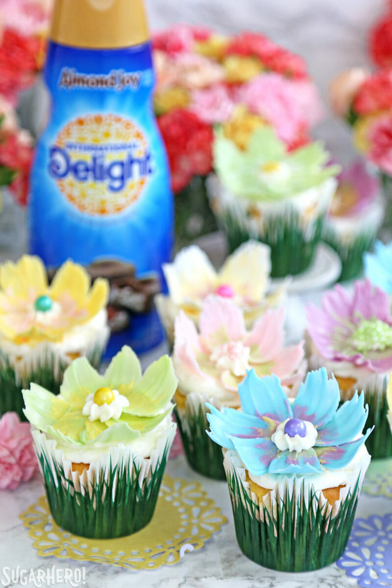 Easy Chocolate Flower Cupcakes - big group of lemon cupcakes with chocolate flowers on top and almond joy creamer bottle and fresh flowers in background | From SugarHero.com