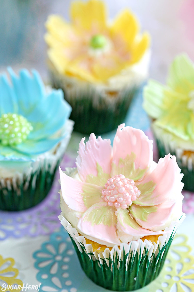 Easy Chocolate Flower Cupcakes - close-up of lemon-coconut cupcake with pink and green chocolate flower on top | From SugarHero.com