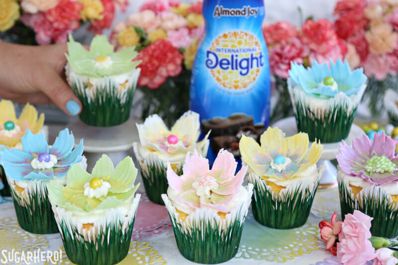 Easy Chocolate Flower Cupcakes - big group of lemon cupcakes with chocolate flowers on top and almond joy creamer bottle in background | From SugarHero.com