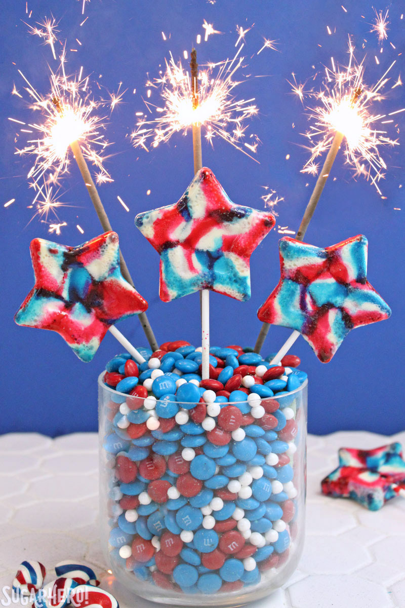 Easy Homemade Lollipops - swirled red, white, and blue lollipops with sparklers behind them | From SugarHero.com