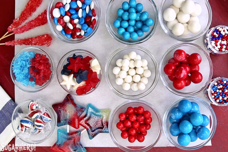 Fourth of July Layer Cake - assorted candies laid out in a flat lay, including red, white, and blue gumballs, M&Ms, gummies, and more | From SugarHero.com