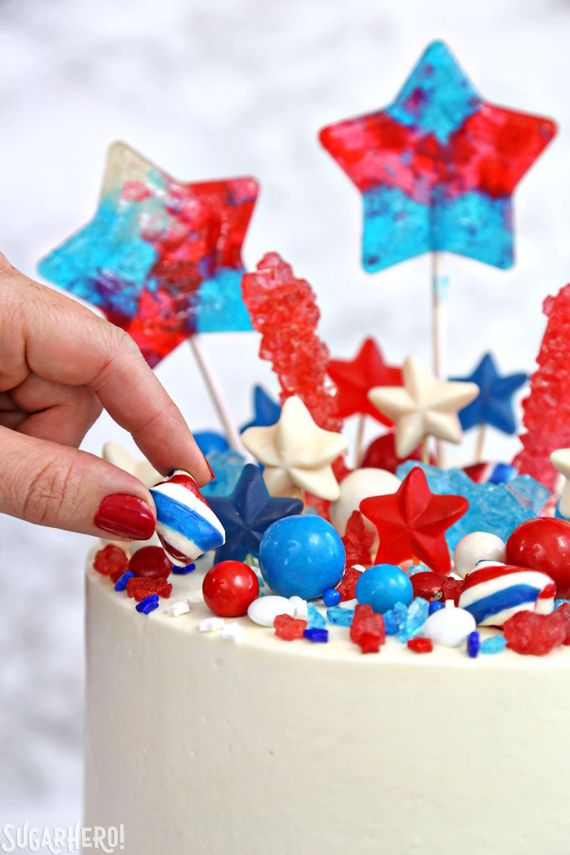 Fourth of July Layer Cake - hand placing mint twist candy on top of cake | From SugarHero.com