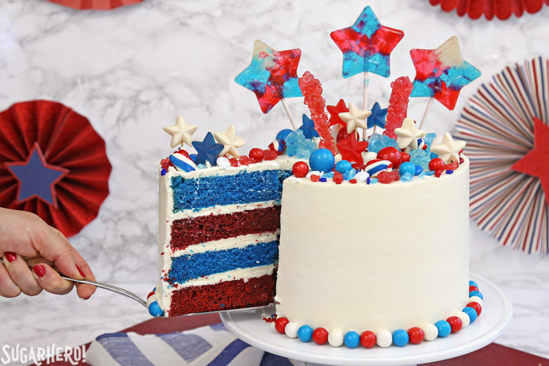 Fourth of July Layer Cake - hand removing a slice of red and blue velvet cake with a cake server | From SugarHero.com