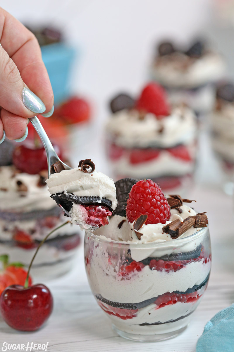 Mini Oreo Icebox Cakes - taking a spoonful of no-bake Oreo cake | From SugarHero.com