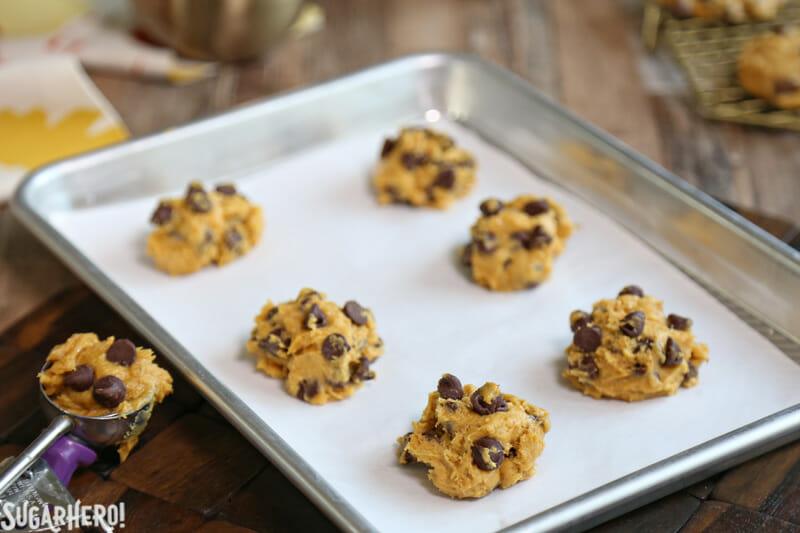 Pumpkin Chocolate Chip Cookies - scoops of pumpkin chocolate chip cookie dough on a baking sheet | From SugarHero.com