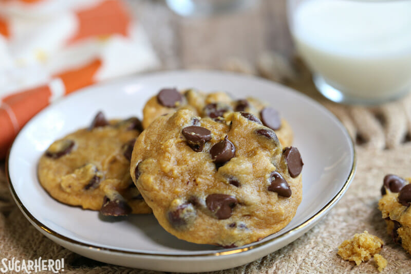 Pumpkin Chocolate Chip Cookies - three chocolate chip cookies on a plate | From SugarHero.com