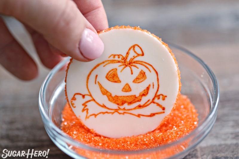 Stamped Halloween Cupcakes - putting a rim of orange sparkling sugar around a fondant circle stamped with an orange pumpkin | From SugarHero.com